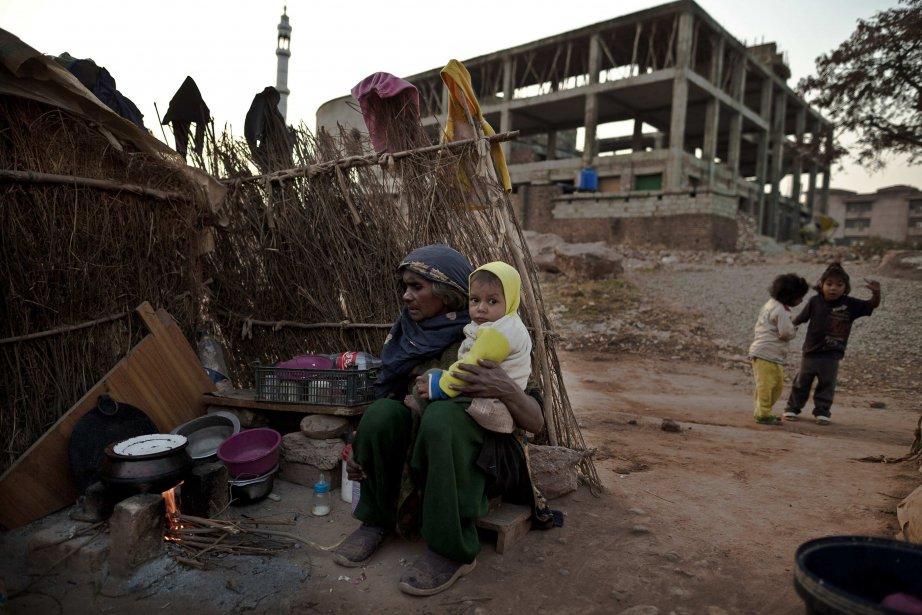 Une femme est assise avec son petit-fils en dehors d'un abri temporaire, près d'une mosquée en construction. | 31 janvier 2013