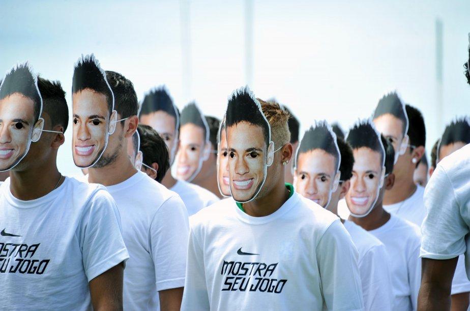Neymar, joueur brésilien de soccer (centre), et un groupe de jeunes hommes portent des masques du visage de Neymar lors de la présentation du nouvel uniforme de l'équipe, à Rio de Janeiro. | 31 janvier 2013