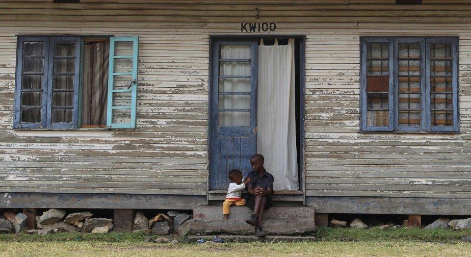 Deux enfants d'employés des mines jouent devant une maison en bois, aux mines de Kilembe dans les contreforts des montagnes de Rwenzori. | 31 janvier 2013