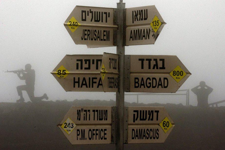 Des soldats israéliens montent la garde à côté d'un panneau routier indiquant les distances à Jérusalem, Bagdad, Damas et autres, à Mont Bental. | 31 janvier 2013