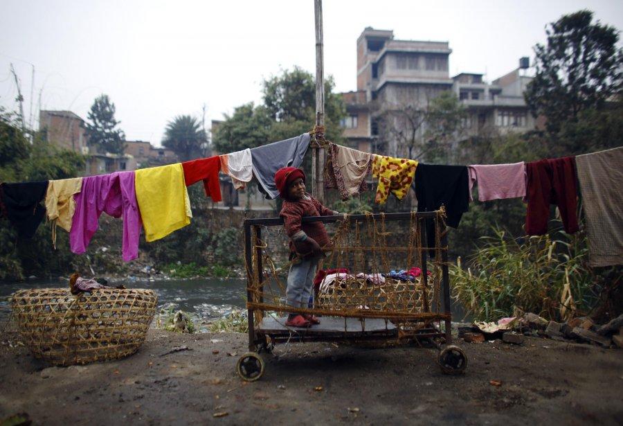 Un enfant joue sur une charrette près de son domicile dans une favela sur les bords de la rivière Bishnumati à Katmandou. | 6 février 2013