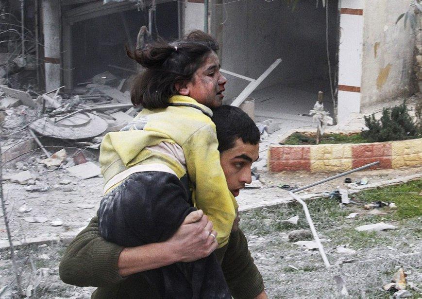 Un adolescent transporte sa soeur blessée lors de frappes aériennes à Alep, le 3 février 2013. | 6 février 2013
