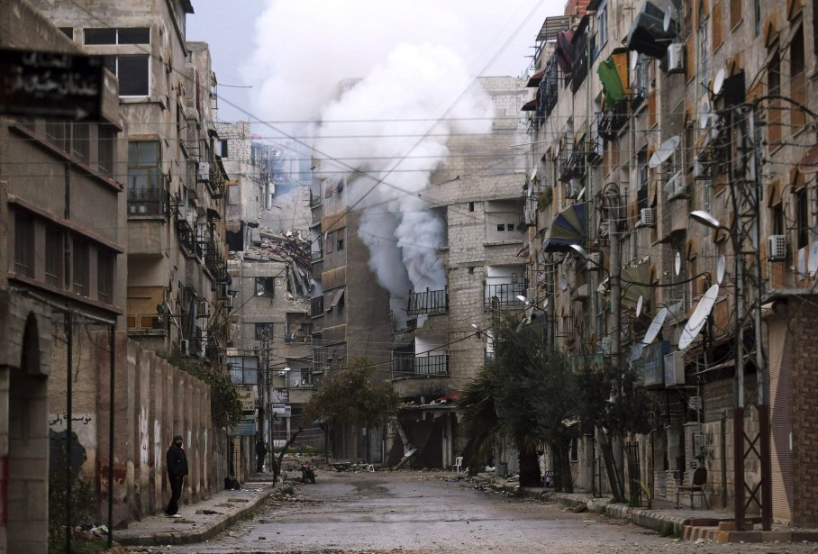 Un homme se promène dans une rue déserte près d'un bâtiment enflammé, dans le quartier Zamalka de Damas, la capitale de la Syrie. | 6 février 2013
