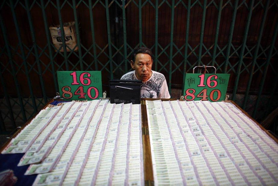 Un homme écoute la radio alors qu'il vend des billets de loterie dans le quartier chinois de Bangkok. | 6 février 2013