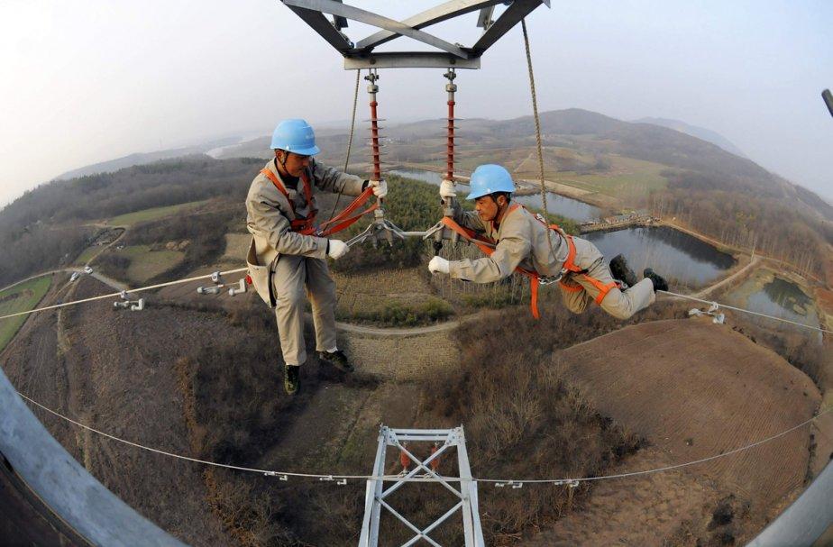 Des électriciens à l'oeuvre sur un pylône de la ville de Chuzhou, en Chine. | 8 février 2013