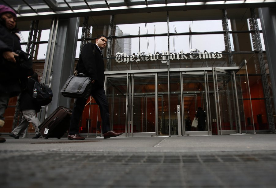 Un homme marche devant la bâtisse du journal The New York Times à New York. The New York Times Co, jeudi, a révélé avoir augmenté du quart ses revenus, alors que de plus de gens paient pour avoir accès au journal virtuel. | 8 février 2013