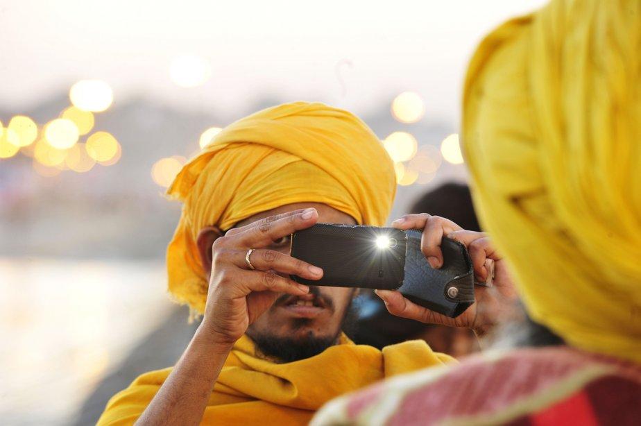 Un Indien prend une photo avec son téléphone mobile pendant le Maha Kumbh Festival à Allahabad. Plus de 100 millions de pèlerins sur une période de 55 jours prendront part à un rituel qui consiste en un bain dans des eaux sacrées, qui purifient. | 8 février 2013