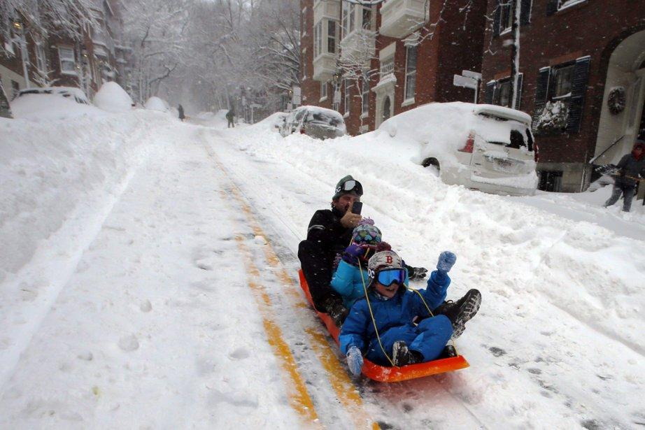 Un père et ses deux enfants profitent de la neige pour glisser dans les rues de Boston, au Massachusetts. | 9 février 2013