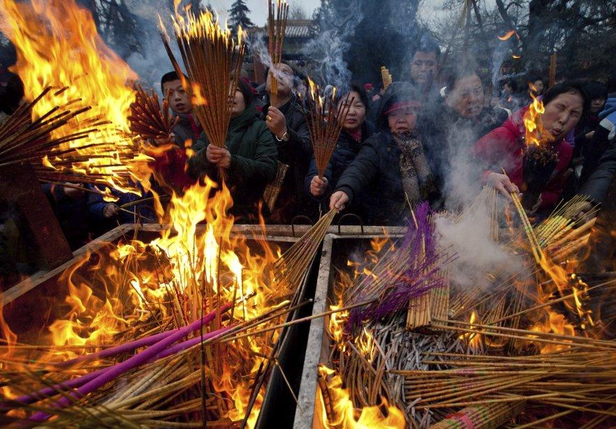 Des croyants brulent de l'encens tout en priant pour la santé et la chance en cette première journée du Nouvel an lunaire en chine, dans le temple de Yonghegong Lama à Pékin, samedi. Des millions de chinois célèbrent ainsi l'arrivée de l'année du Serpent. | 10 février 2013