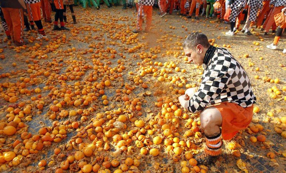 Un participant au carnaval d'Ivrea, en Italie, ramasse des oranges... | 2013-02-11 00:00:00.000