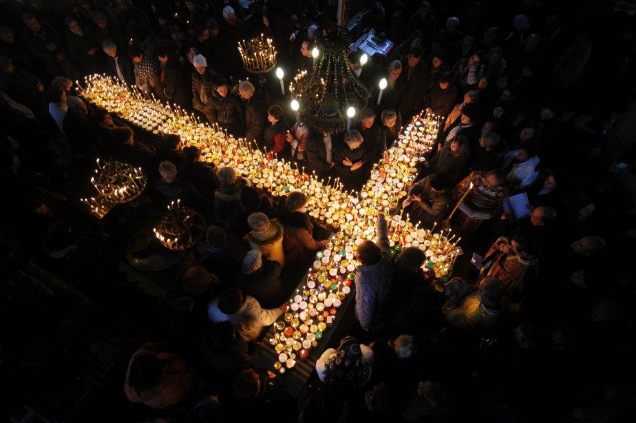 Des fidèles prient autour d'une croix formée de bougies posées sur des pots de miel. La célébration est donnée en l'honneur de Saint-Haralampi, protecteur des apiculteurs. | 11 février 2013