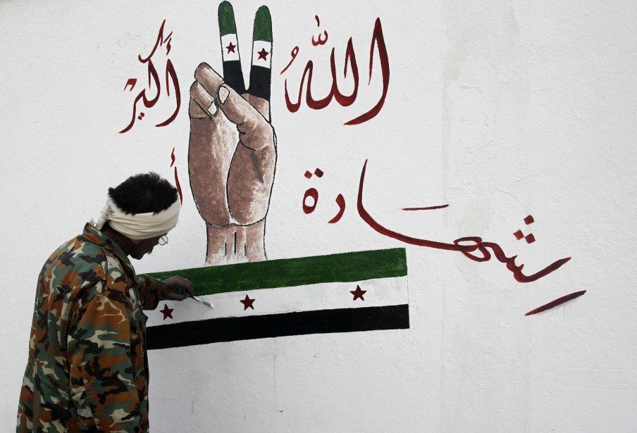 Un membre de l'armée rebelle syrienne peint sur le mur d'une école à Alep. | 11 février 2013