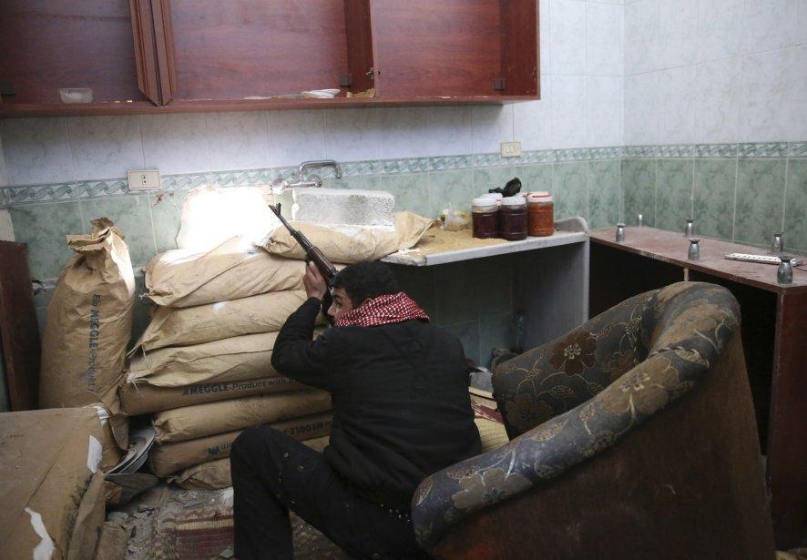 Un soldat de l'Armée syrienne libre se positionne dans une maison lors d'affrontements avec des combattants fidèles au président syrien Bashar al-Assad, dans le quartier Arabeen de Damas. | 13 février 2013