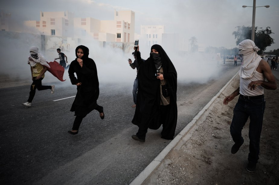 Des manifestants se mettent à l'abri des gaz lacrymogènes lors d'un rassemblement antigouvernemental exigeant des réformes, au village de Sanabis, à l'ouest de la capitale Manama, au Bahreïn. | 13 février 2013