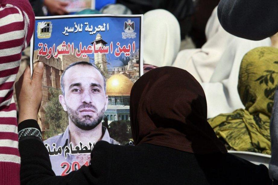Une femme tient la photo du prisonnier palestinien... (PHOTO d'archives NASSER SHIYOUKHI, AP)