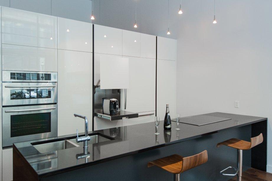 Dans la cuisine, très épurée. les électroménagers sont tous encastrés. Les armoires laquées, taillées en biseau, n'ont pas de poignée. Le réfrégirateur est à peine visible. | 14 février 2013