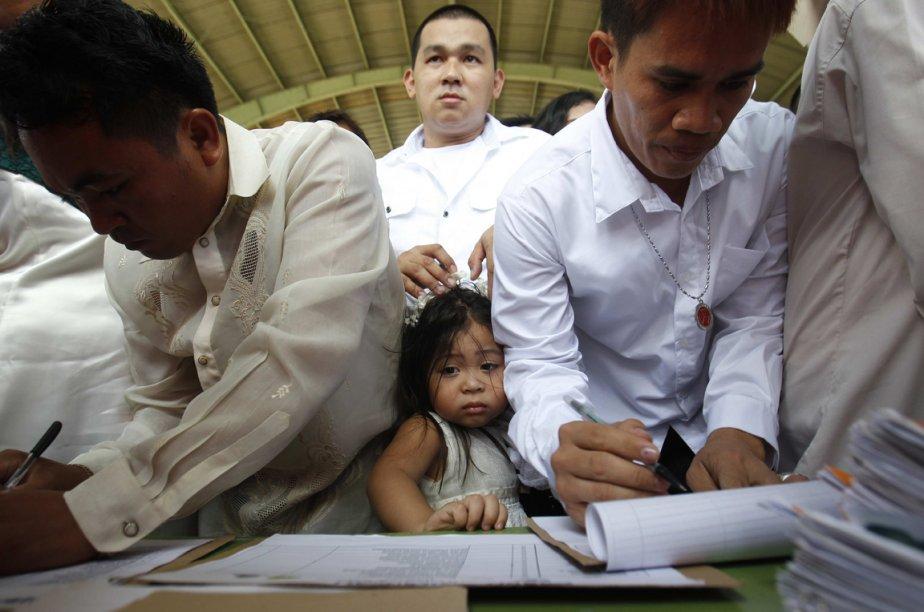 Une fillette coincée entre deux futurs mariés avant une cérémonie de mariage collectif à Manille, aux Philippines. | 15 février 2013