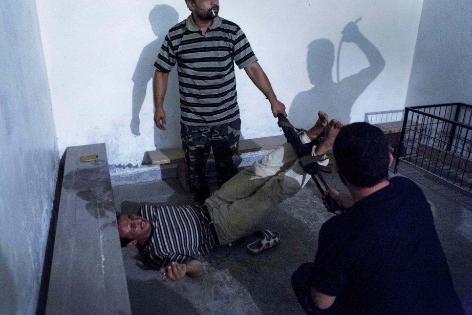 Le deuxième prix dans la catégorie «nouvelles» va à Emin Ozmen pour cette photo montrant des rebelles syriens interroger et torturer un sympathisant du régime. | 15 février 2013