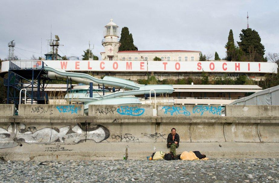 Un homme assis au milieu de ses possessions sur la plage, sous un écriteau qui clame «Bienvenue à Sotchi». À un an des jeux d'hiver, les travaux de construction et les expropriations continuent alors que les tests des installations et diverses championnats mondiaux battent leur plein. | 19 février 2013