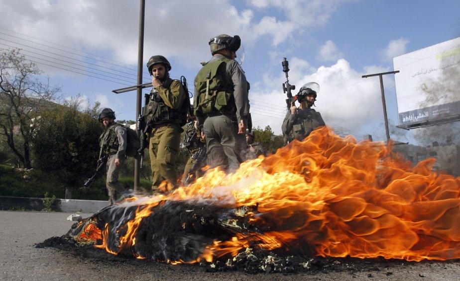 Des soldats israéliens et des gardes-frontières près d'un feu de pneus allumé par des lanceurs de pierres palestiniens durant des affrontements au point de contrôle de Hawara, dans Jérusalem-Ouest. Les Palestiniens de ce quartier de la ville sainte ont tenu des manifestations lundi en solidarité avec des grévistes de la faim détenus dans les prisons israéliennes. | 19 février 2013