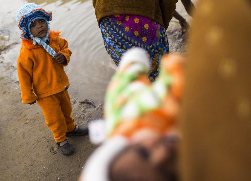 Un enfant observe sa famille avant le bain rituel dans le Gange durant les festivités du Kumbh Mela à Allahabad. | 19 février 2013
