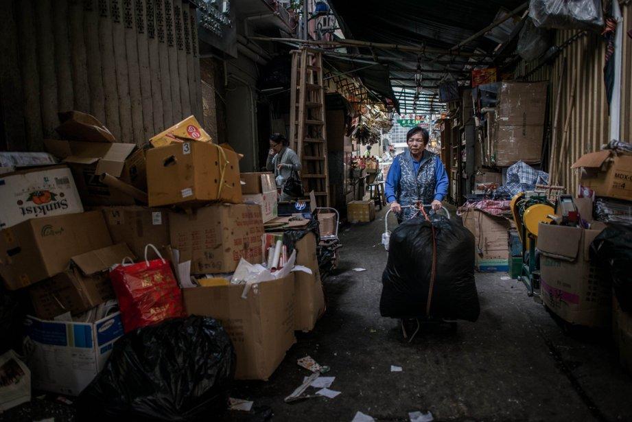 Une femme pousse un chariot rempli de matières à recycler à Hong Kong. Des militants dénoncent depuis des années le retard qu'a pris Honk Kong par rapport au reste du monde en matière de protection de l'environnement, qu'il s'agisse de recyclage ou d'aménagement de pistes cyclables. | 21 février 2013