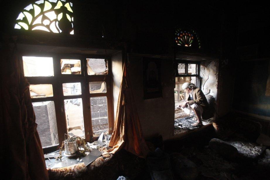 Un homme observe de sa fenêtre les dégâts causés par l'écrasement d'un avion militaire à Sanaa, au Yémen. | 21 février 2013