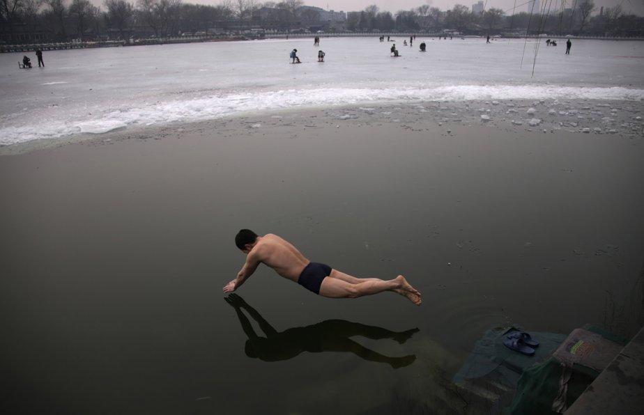 Un nageur plonge dans les eaux glacées du lac Houhai, à Pékin. | 21 février 2013