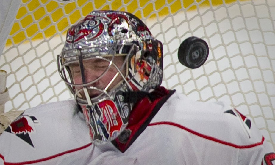Le gardien Cam Ward, des Hurricanes de la Caroline, reçoit une rondelle de hockey sur son masque lors d'un match contre le Canadien de Montréal. | 21 février 2013