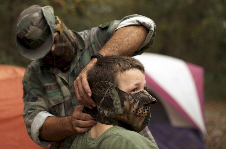 Un membre du North Florida Survival Group attache un masque sur le visage de son fils en préparation d'un exercice de survie. | 22 février 2013