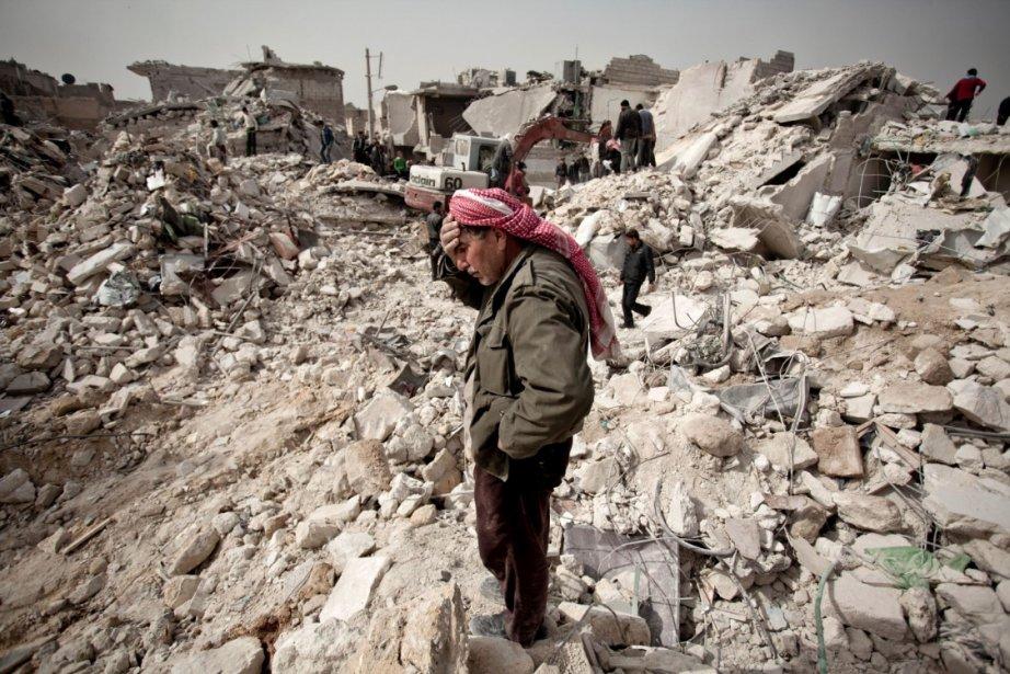 Un homme se tient debout, impuissant, au milieu des ruines de sa maison alors que d'autres cherchent désespérément des survivants… ou des corps. Les forces syriennes ont lancé trois missiles sur le quartier Tariq Al-Bab d'Alep, samedi, faisant au moins 58 morts, dont 36 enfants. | 24 février 2013