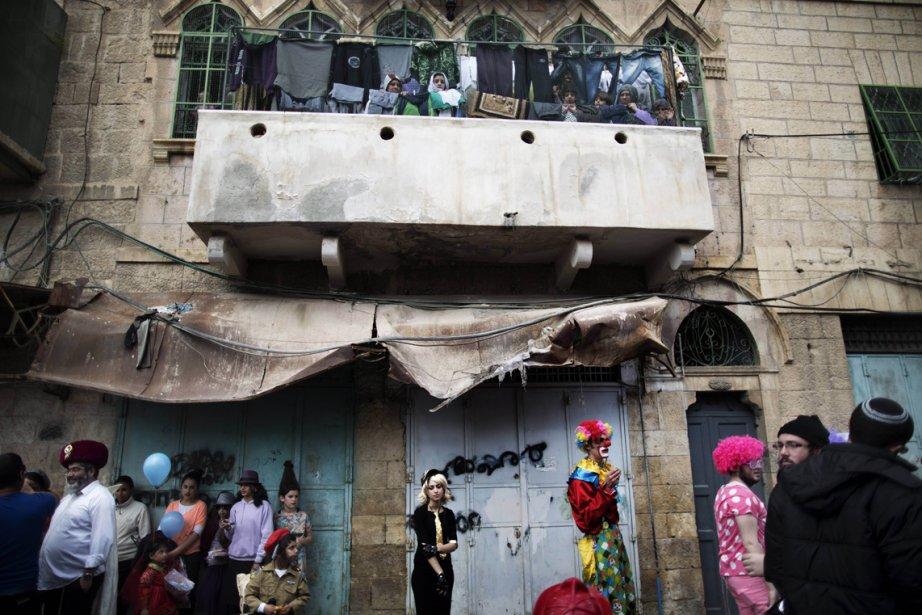 Des Palestiniens observent de leur balcon le défilé de Pourim dans la ville occupée d'Hébron. Cette fête juive commémore les événements relatés dans le Livre d'Esther, lorsque les Juifs ont échappé à leur extermination par le régime de la Perse antique. | 25 février 2013