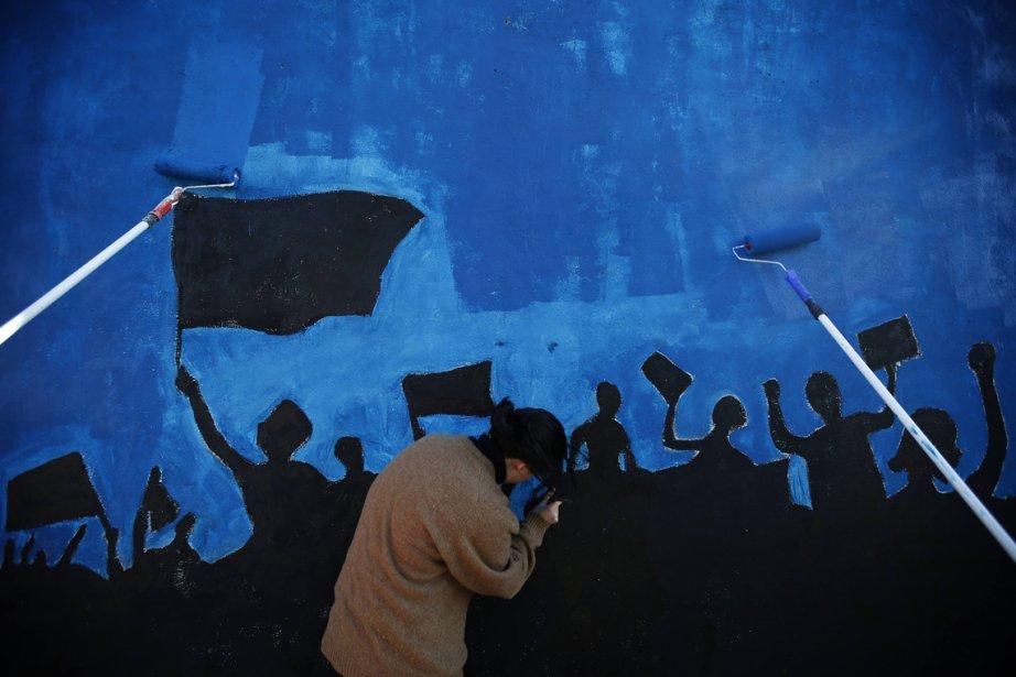 Des membres du mouvement «Troïka maudite» travaillent à une murale appelant à une manifestation à Lisbonne pour protester contre les mesures d'austérité imposées au Portugal par l'Union européenne, le FMI et la Banque centrale européenne. De telles manifestations doivent avoir lieu dans tout le Portugal le 2 mars. | 25 février 2013