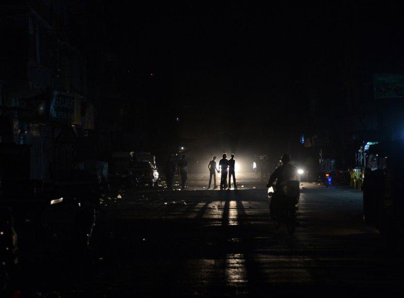 De jeunes Pakistanais traversent une rue durant une panne d'électricité qui a frappé le pays au complet, dimanche, pendant plus de deux heures, en raison d'un bris dans une centrale importante. | 25 février 2013
