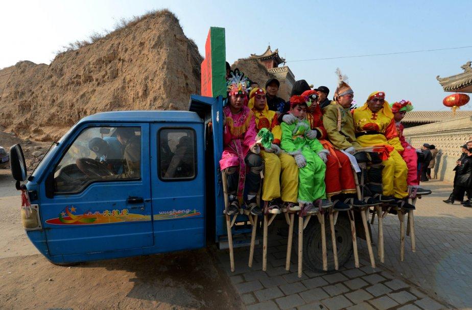 Des échassiers chinois attendent leur transport vers un défilé à l'occasion de la fête des Lanternes, qui a lieu au 15e jour de la nouvelle année lunaire à Nuanquan. La fête, vieille de plus de 2000 ans, voit toutes les villes de Chine se transformer en mer de lanternes et de feux d'artifice. | 25 février 2013