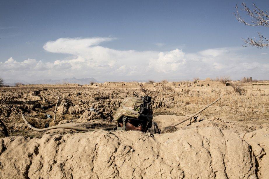 Un soldat américain de la 3e compagnie, 3e Bataillon, 1re Division blindée, regarde par dessus un mur de terre lors de sa patrouille du village de Layadira, province de Kandahar, en Afghanistan. | 25 février 2013