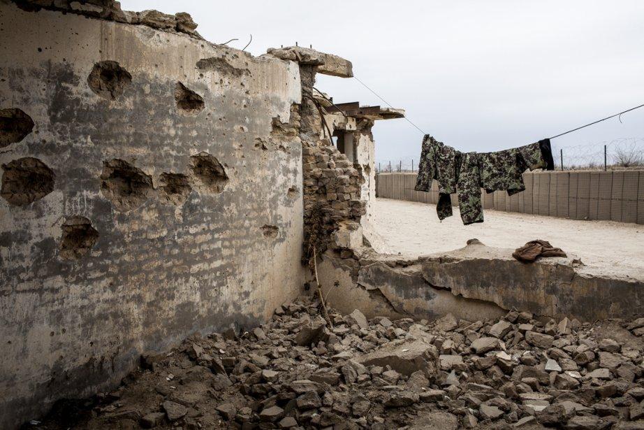 Des soldats de l'Armée nationale afghane des vêtements à l'extérieur d'un bâtiment qui abritait autrefois une salle de classe dans le village Tieranon, en Afghanistan. | 25 février 2013