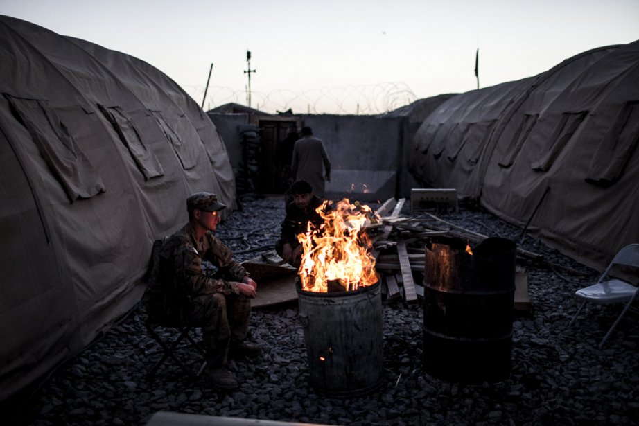 Un soldat américain de la 3e compagnie, 3e Bataillon, 1re Division blindée, s'assoit près d'un feu au poste de Strong Point Haji Rahmuddin II, dans la province de Kandahar, en Afghanistan. | 25 février 2013