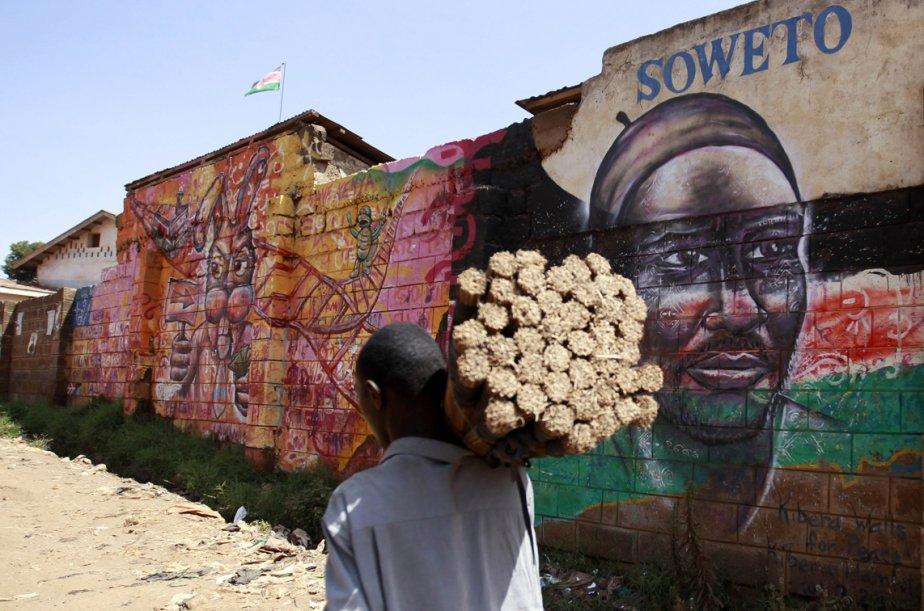 Un homme vend des balais en marchant le long d'une murale qui évoque la paix dans le bidonville de Kibera, à Nairobi au Kenya. | 26 février 2013