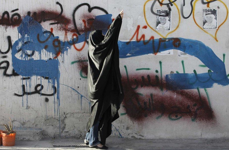 Une manifestante crie des slogans antigouvernementaux à la police antiémeute lors d'affrontements dans le village de Bilad-al-Qadeem, au sud de Manama. | 26 février 2013