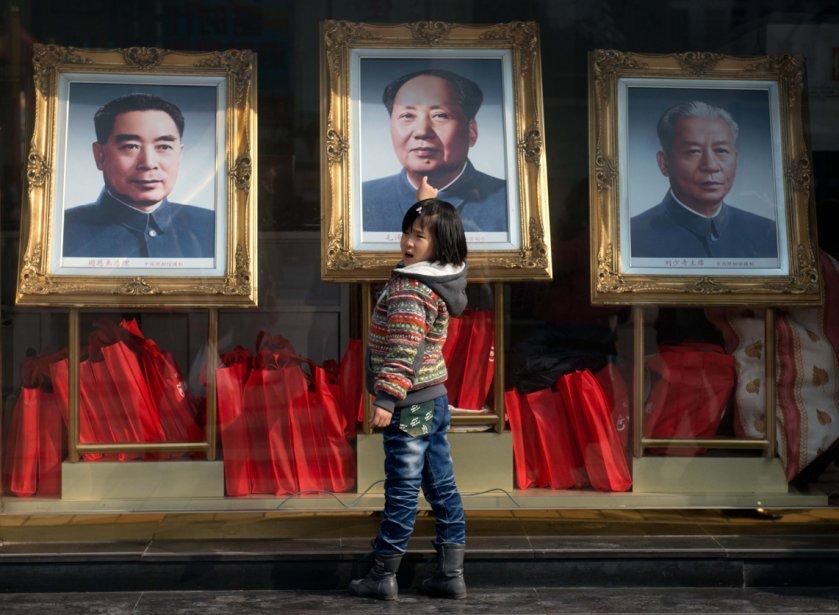 Un fillette regarde les portraits des anciens dirigeants chinois ... | 2013-02-27 00:00:00.000