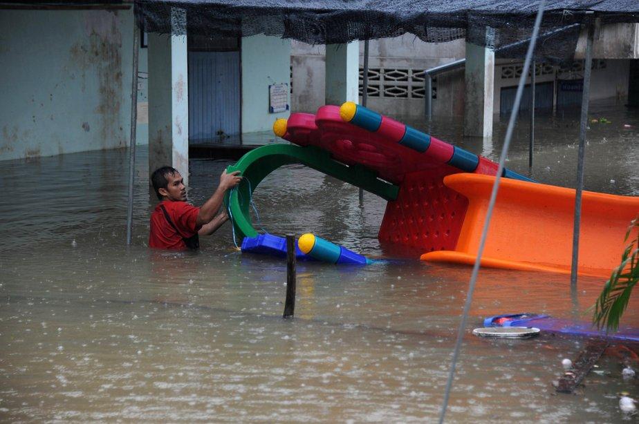 Un homme essaie de tirer une glissoire pour enfants hors de l'eau après les pluies torrentielles qui ont inondé la province de Narathiwat, dans le sud de la Thaïlande. Cette région du pays, près de la frontière de la Malaisie, est quotidiennement le théâtre d'attaques armées de la part d'insurgés qui réclament plus d'autonomie. | 27 février 2013