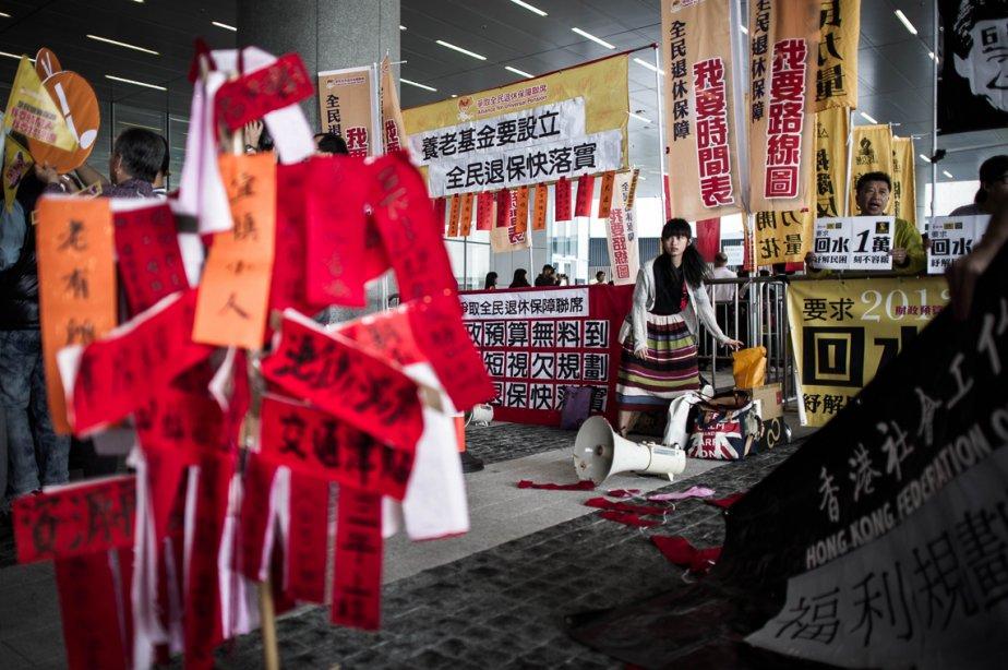 Une manifestante au milieu de bannières avant la présentation du budget par le secrétaire des Finances de Hong Kong, John Tsang. On s'attend à une croissance modeste de l'économie hongkongaise en raison d'exportations moindres, a annoncé M. Tang, donc le budget visait surtout à juguler la hausse vertigineuse du marché immobilier. | 28 février 2013