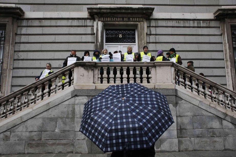 Des membres du mouvement de retraités Yayoflautas prennent la pose pour un photographe réfugié sous un parapluie devant l'archevêché de Madrid. Les membres de Yayoflautas reprochent à l'Église catholique d'Espagne d'être plus proche des privilégiés que des personnes dans le besoin. | 28 février 2013