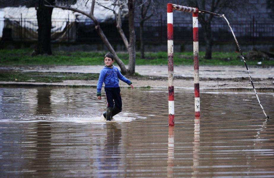 Un garçon traverse la cour de son école inondée à Murtino, à 180 km au nord de Skopje, capitale de la Macédoine, où deux jours de pluies torrentielles ont inondé plusieurs centaines de maisons et fait un mort. | 28 février 2013