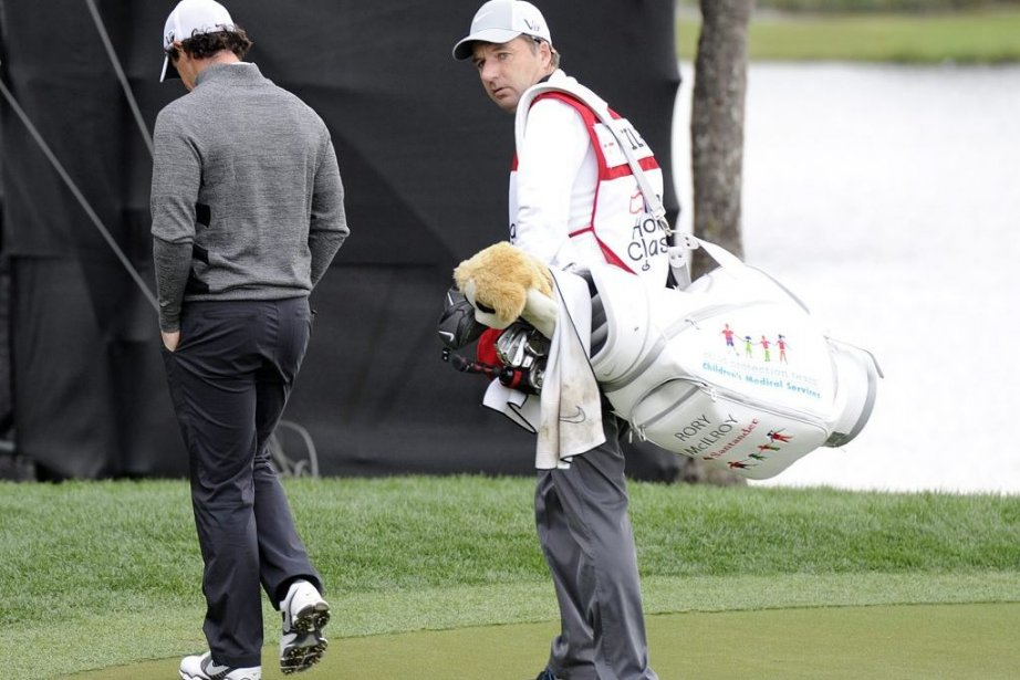Rory McIlroy quitte le parcours en compagnie de... (PHOTO DOUG MURRAY, REUTERS)