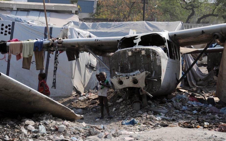 Des enfants jouent près de la carcasse d'un avion léger dans un camp de déplacés à Port-au-Prince, en Haïti. Les Nations unies mènent toujours une vaste mission de maintien de la paix dirigée par le Brésil dans ce pays ravagé par le tremblement de terre de janvier 2010 et miné par des querelles politiques. | 1 mars 2013