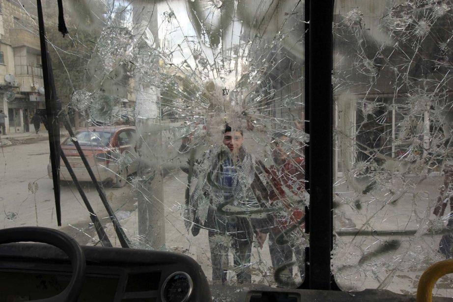 Garçons vus à travers un pare-brise fracassé dans une rue d'Alep, en Syrie. | 1 mars 2013