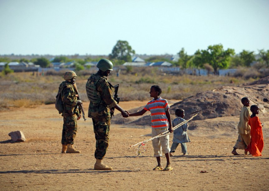 Un petit Somalien salue un soldat ougandais en mission avec l'Union africaine en Somalie, à Buur-Hakba. L'armée nationale somalienne, avec le soutien des forces de l'Union africaine, avait repris cette ville la veille des mains du groupe extrémiste Al Shabaab, affilié à Al-Qaïda. | 1 mars 2013