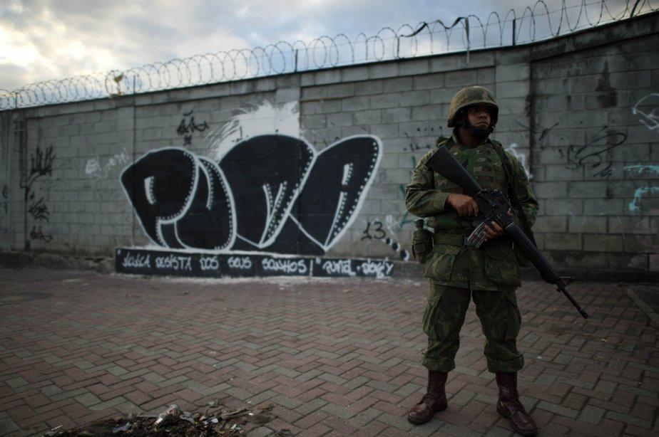 Un soldat brésilien monte la garde à l'entrée du bidonville de Caju à Rio de Janeiro, au Brésil, au cours d'une opération de pacification. | 4 mars 2013
